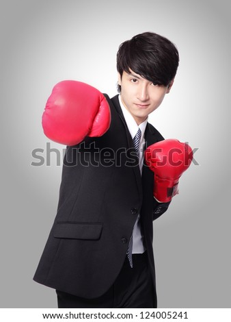 successful businessman punching and hitting with boxing gloves isolated on gray background,  Business competition concept, asian model - stock photo