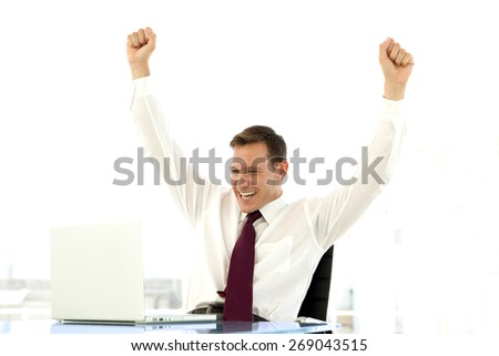 Successful businessman raising arms at workplace - stock photo