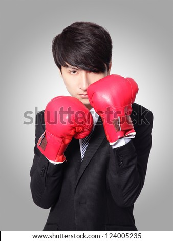 successful businessman ready punching with boxing gloves isolated on gray background,  Business competition concept, asian model - stock photo