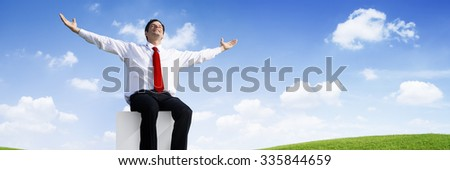 Successful Businessman Relaxing in an Open Field - stock photo