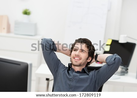 Successful businessman relaxing in his chair leaning back with his hands behind his head looking into the air smiling - stock photo