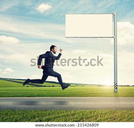 successful businessman running on the road against empty billboard and green field - stock photo