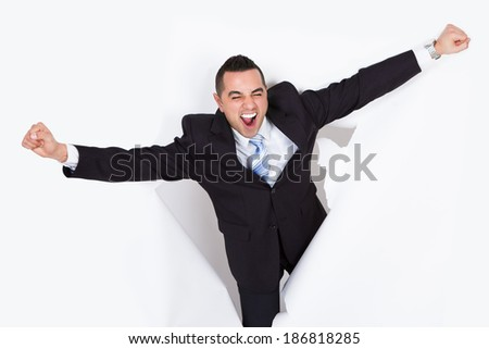 Successful businessman shouting while breaking through white paper wall
