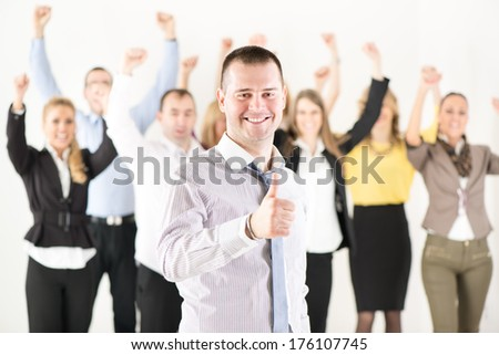 Successful businessman showing Thumbs Up standing in front of happy colleagues and looking at the camera. - stock photo