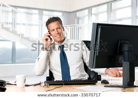 Successful businessman sit at his desk while talking on mobile - stock photo