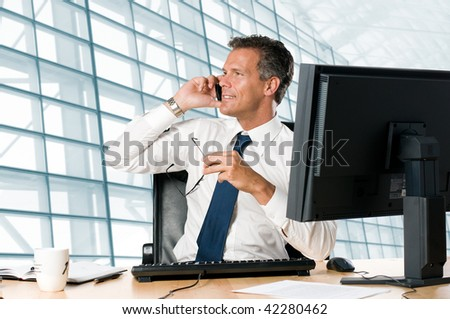 Successful businessman sit at his desk while talking on mobile in office - stock photo