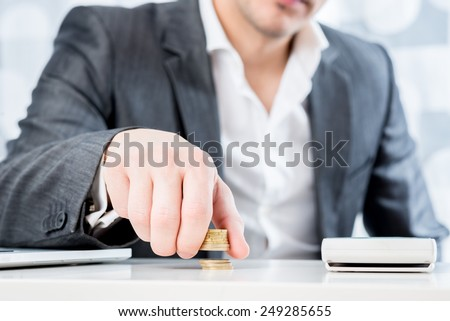 Successful businessman sitting at his desk counting gold coins in a conceptual image, closeup view of his torso with focus to his hand. - stock photo