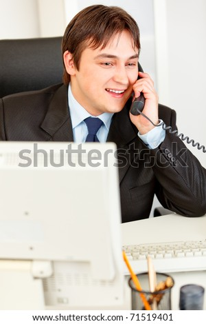Successful businessman sitting at office desk and talking on phone - stock photo