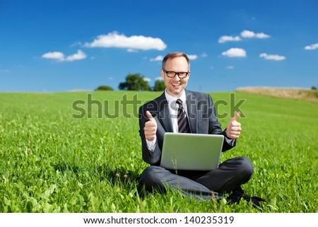 Successful businessman sitting cross legged in a grassy green field giving a thumbs up of approval for his beautiful outdoor office under a sunny blue sky - stock photo