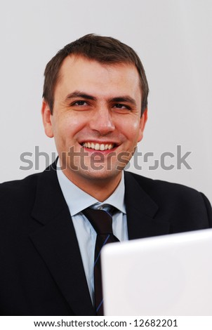 Successful businessman sitting on a table with lap-top and smiling