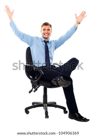 Successful businessman sitting on chair and posing with arms up