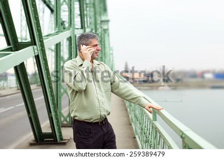 Successful businessman standing on bridge and calling outdoor - stock photo