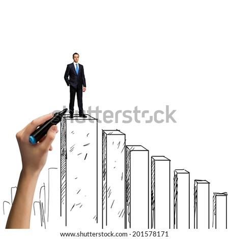 Successful businessman standing on drawn graph bars - stock photo