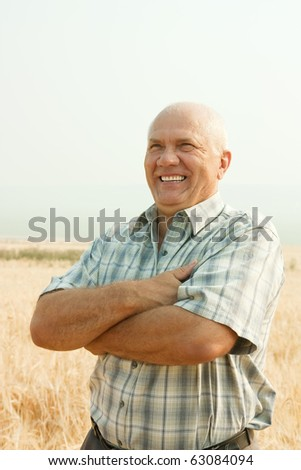 successful businessman standing outdoor on field of wheat - stock photo