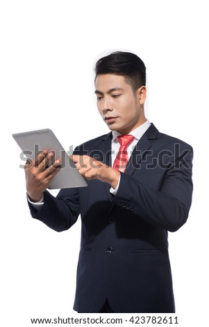 Successful businessman standing using a tablet to access the internet as he leans against a white with copyspace