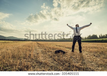 Successful businessman standing victoriously in the middle of field raising his arms in celebration and relief as he stands under majestic evening sky with his jacket lying on the floor next to him. - stock photo