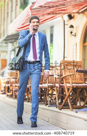 Successful businessman talking by mobile phone and walking at street near french cafe. Early morning. Urban, city life. Happy intelligent man. - stock photo