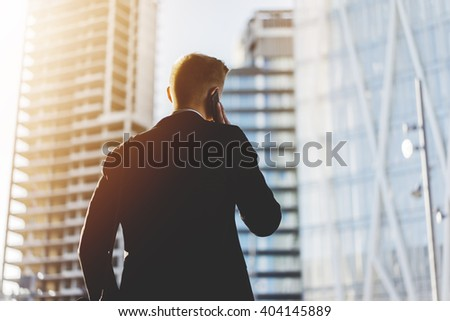 Successful businessman talking on his smartphone while working on new project of building modern house or business centre outdoors, flare light - stock photo
