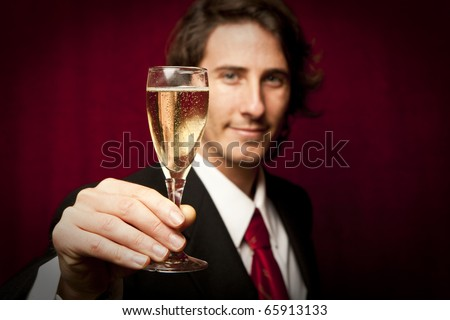 Successful businessman toasting with Champagne against a red background
