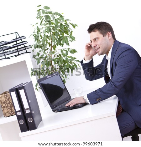Successful businessman using cellphone in his office