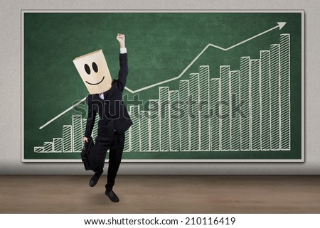 Successful businessman wearing cardboard head celebrating success in front of business graph