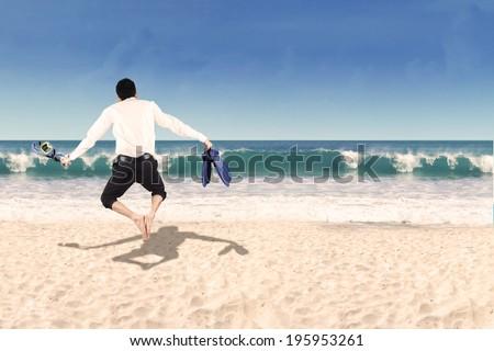 Successful businessman wearing snorkeling gear jumping on beach - stock photo