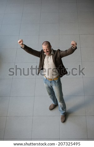 Successful businessman with arms up celebrating his victory. Top view - stock photo
