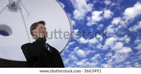 Successful businessman with cell phone in front of a huge satellite dish - stock photo
