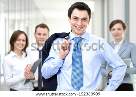 Successful businessman with colleagues in the background - stock photo