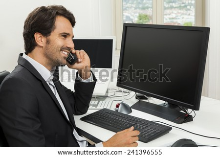 Successful businessman working in his office sitting in a chair at his desk and desktop computer listening to a call on his mobile phone, high angle side view - stock photo