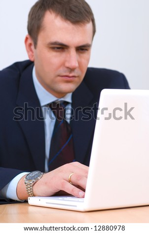 Successful businessman working on laptop, focus on hands