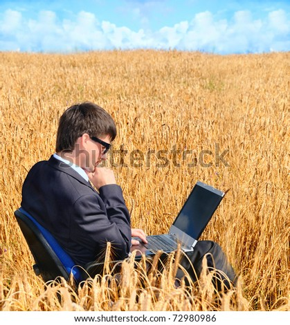 successful businessman works in field on notebook - stock photo