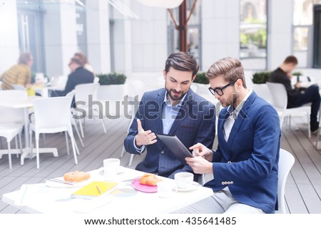 Successful businessmen are using gadget for work - stock photo