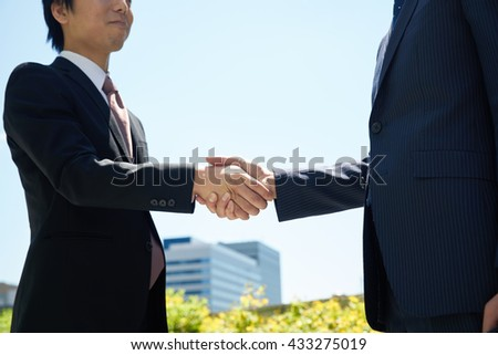 Successful businesspeople shake hands against the sky - stock photo
