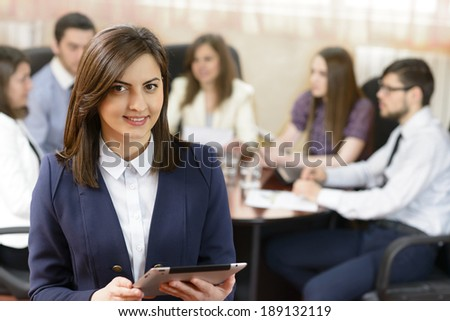 Successful businesswoman at the office leading a group - stock photo