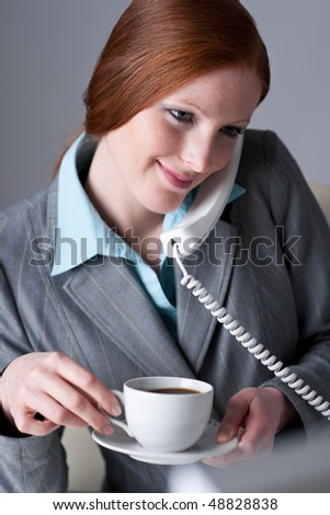 Successful businesswoman calling on the phone at office, having coffee