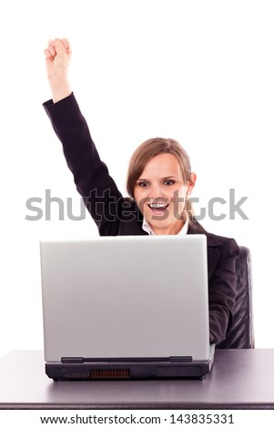Successful businesswoman celebrating victory while sitting at office desk  isolated over  white background