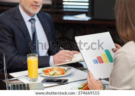 Successful businesswoman has a business lunch with her client in cafe. They are working with documents with concentration - stock photo