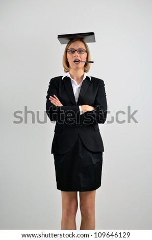 Successful businesswoman holding a folder on her head and biting a pen - stock photo
