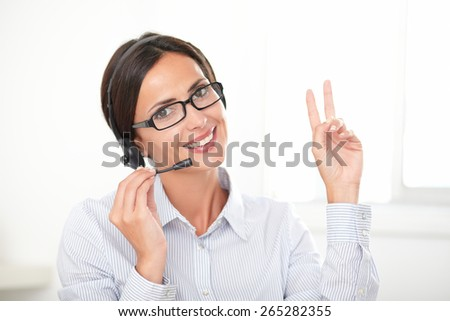 Successful businesswoman in blue blouse speaking on the headphones while smiling and looking at you - stock photo