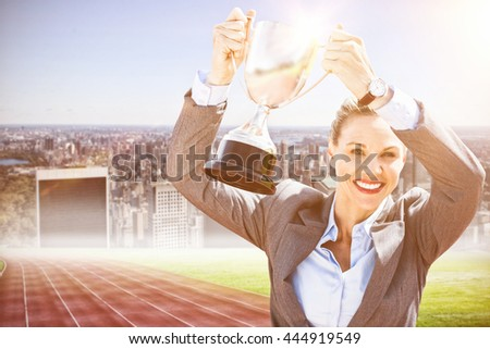 Successful businesswoman lifting a trophy against composite image of track against city - stock photo