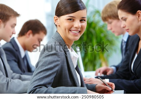 Successful businesswoman looking at camera on background of working colleagues - stock photo