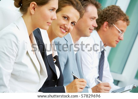 Successful businesswoman looking at camera while working between partners - stock photo