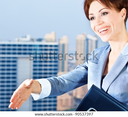 Successful businesswoman making a deal, young smart office worker, woman over blue sky & city background, handshake, business lifestyle concept - stock photo