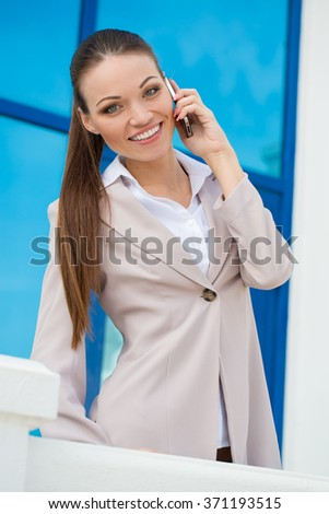 Successful businesswoman or entrepreneur taking notes and talking on cellphone while walking outdoor. - stock photo