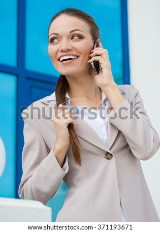 Successful businesswoman or entrepreneur taking notes and talking on cellphone while walking outdoor.