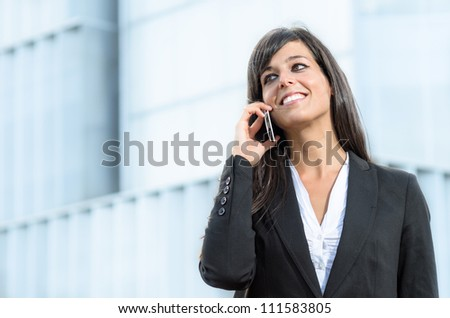 Successful businesswoman or entrepreneur talking on the cellphone outside. Beautiful woman on business conversation on the phone.