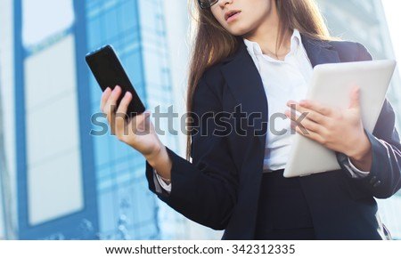 Successful businesswoman or entrepreneur using a digital tablet computer and talking on cellphone standing in front of his office. - stock photo