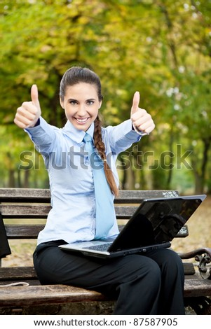 successful businesswoman outdoor showing thumbs up - stock photo