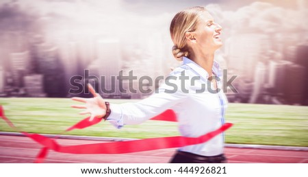Successful businesswoman raising arms against running track in front of city - stock photo